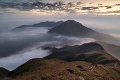 Moln som rullar över ett berg på den Lantau ön på gryning Arkivfoton