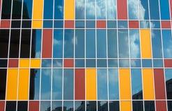 Moln som svävar i himlen, reflekterade i exponeringsglaset av en skyskrapa Arkivbilder