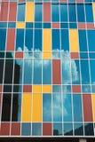 Moln som svävar i himlen, reflekterade i fönstren av en skyskrapa Arkivfoton