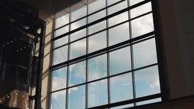 Moln svävar utanför den fönsterbyggnadsTid schackningsperioden stock video