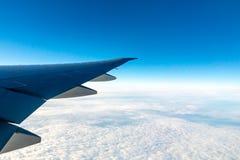Moln under vingen av ett flygplan Förbluffa sikt från fönstret av flygplanet under flyget royaltyfri fotografi
