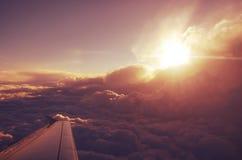 Moln uppifrån och dramatisk solnedgång, flygplansikt Arkivfoto
