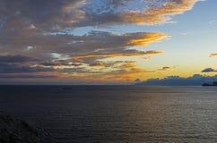 Moln ?ver havet exponerat av inst?llningssolen arkivbilder