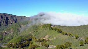 Molndrivor över frodigt landskap och vulkaniska berg arkivfilmer