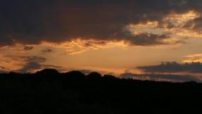 Molnen flyttar sig snabbt mot bakgrunden av en orange härlig solnedgång stock video