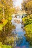 Molnen och bron reflekterade i dammet, parkera av godset Mikhailovskoe, Pushkinskiye berg Royaltyfria Bilder