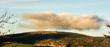 Molnhängningar ovanför toppmötet av Brocken i den tyska Harzen arkivfoton