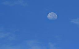 Molnhimmeldag och månen Arkivbild