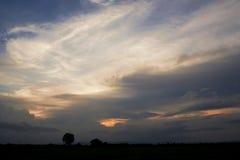 Molnig aftonhimmel och solnedgång Arkivbild
