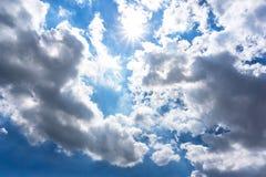 Molnig blå himmel- och solbakgrund royaltyfria foton