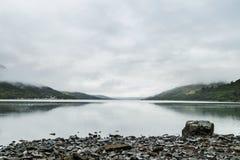 Molnig dag på en grå sjö arkivfoto