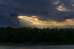 Molnig dramatisk solnedgång över vatten Royaltyfri Foto