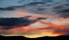 molnig färgrik skysolnedgång Arkivbild