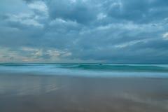 Molnig gryningSeascape på stranden royaltyfri fotografi