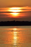 Molnig guld- dold sol för sjösolnedgång delvist Royaltyfria Bilder