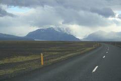 Molnig himmel över berg i Island Arkivbild