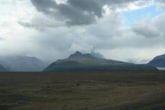 Molnig himmel över berg i Island Arkivfoton