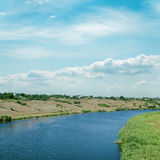 Molnig himmel över floden arkivfoto