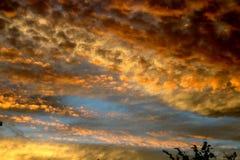 Molnig himmel för dramatisk solnedgång med moln som tänds av solnedgångsolljus royaltyfria bilder