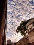 Molnig himmel i staden arkivbild