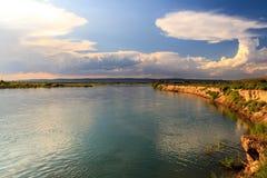 Molnig himmel och flod i grönt landskap Fotografering för Bildbyråer