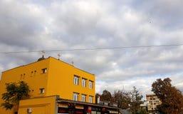 Molnig himmel och gula byggnader royaltyfri bild