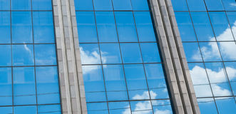 Molnig himmel reflekterade i fönstren av ett byggnadskontor Royaltyfri Bild