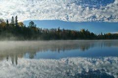 Molnig himmel som reflekterar på en Autumn Lake Royaltyfria Foton