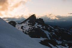 Molnig lynnig solnedgång i snöberg ovanför Garibaldi Lake på panorama Ridge fotografering för bildbyråer