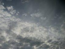 Molnig mulen himmel med solljus som igenom kikar royaltyfri bild