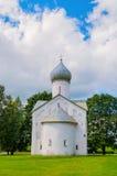 Molnig sikt för arkitektursommar av den forntida kyrkan av de tolv apostlarna på avgrunden i Veliky Novgorod, Ryssland Royaltyfri Foto