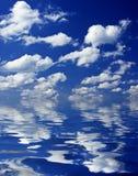 Molnig sky som reflekterar i vatten Arkivfoton