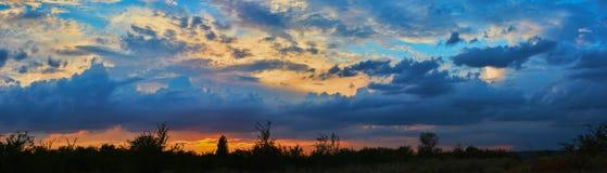 molnig skysolnedgång royaltyfri bild