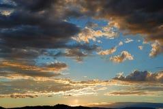 molnig skysolnedgång arkivbild