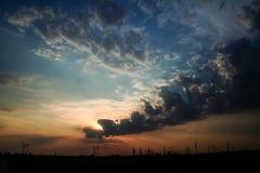 molnig skysolnedgång Arkivbilder