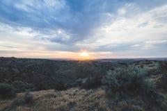 Molnig solnedgång över ökenutlöpare Arkivbilder