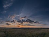 Molnig solnedgång över fältet Arkivbilder