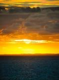 Molnig solnedgång i havet. Arkivbild