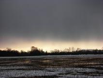 Molnig solnedgång på det snöig fältet Arkivfoton