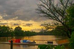 Molnig solnedgång på floden royaltyfria foton