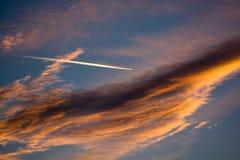 Molnig solnedgånghimmel med flygplanet Fotografering för Bildbyråer