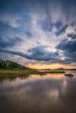 Molnig solnedgångtid vid en sjö Arkivfoto