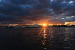 Molnig soluppgång över vatten arkivfoto