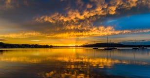Molnig soluppgång Waterscape på fjärden med reflexioner royaltyfria bilder