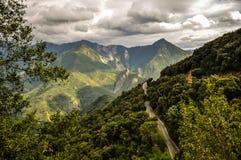 Molnig väg i berg Arkivbilder