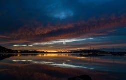 Molniga Dawn Waterscape på fjärden med reflexioner royaltyfri bild