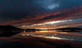 Molniga Dawn Waterscape på fjärden med reflexioner arkivbild