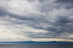 Molniga himlar över vatten Arkivfoto