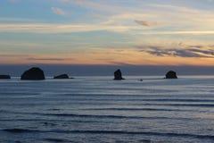 Molniga himlar och solnedgången över Oregon seglar utmed kusten steniga utlöpare för Stilla havet Royaltyfria Bilder