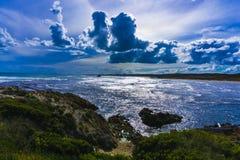 Molnigt bildande över stranden med en blå dragning Royaltyfri Bild